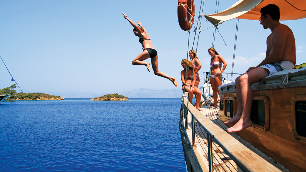 Adventures in Europe - Image of a girl jumping off a sailing boat in Turkey
