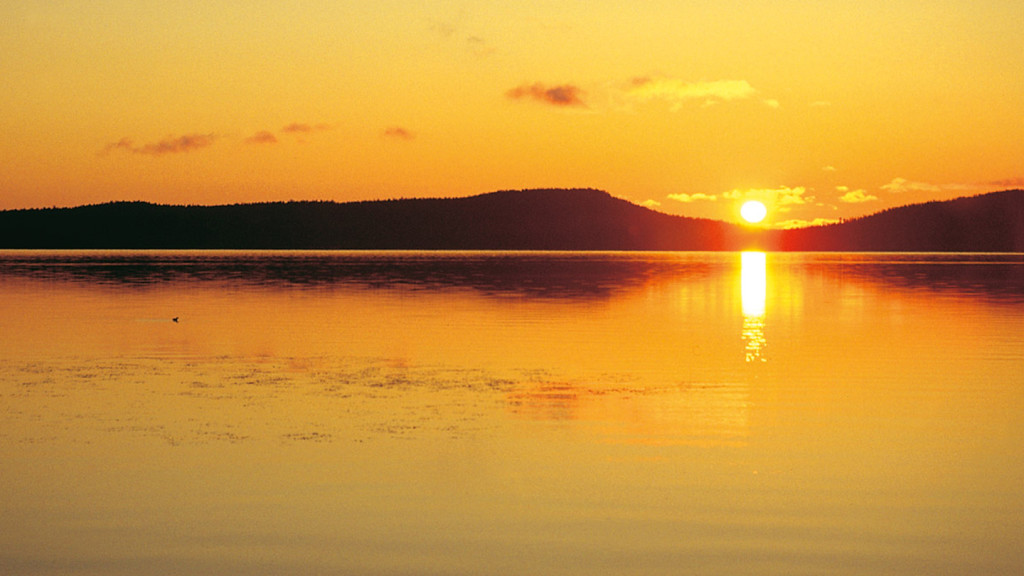 Image of the midnight sun over a lake