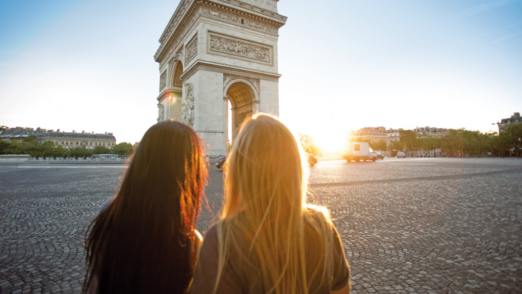 Two girls looking at the Arc De Triomphe at sunrise