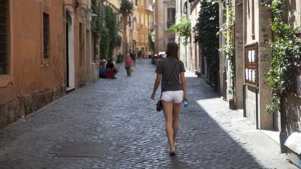 Image of a girl walking a cobbled street in Rome