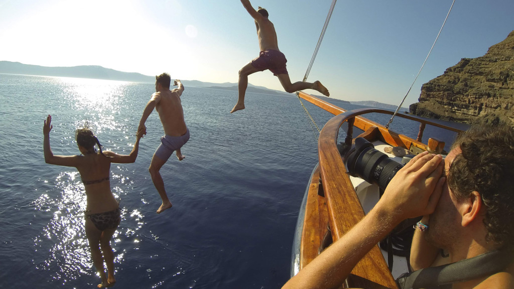Image of three people jumping off a boat into the ocean