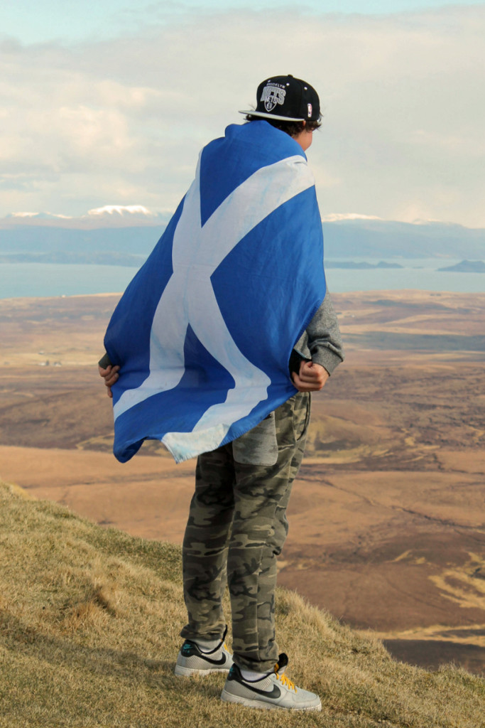 Bonnie Scotland: A Photo Essay - Image of a man overlooking a loch wrapped in a Scottish flag