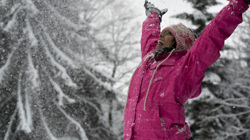 image of a girl raising her arms to the sky in the snow