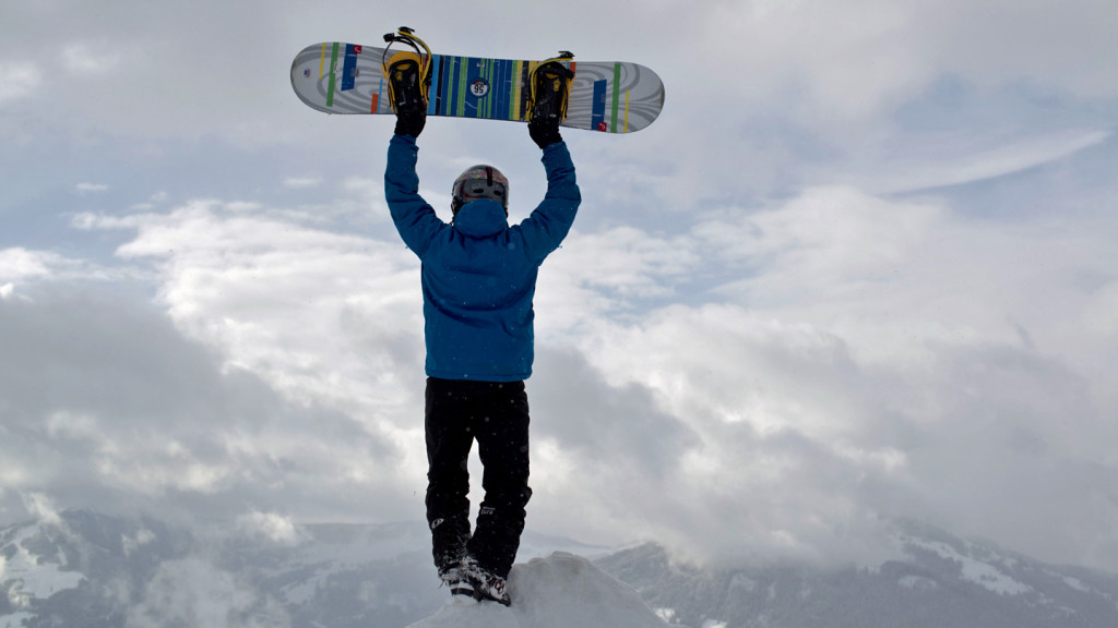 image of a snowboarder holding his board above his head