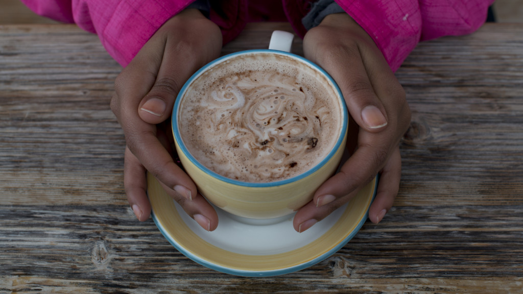 aerial shot of a girls hands cupping a mug of hot chocolate