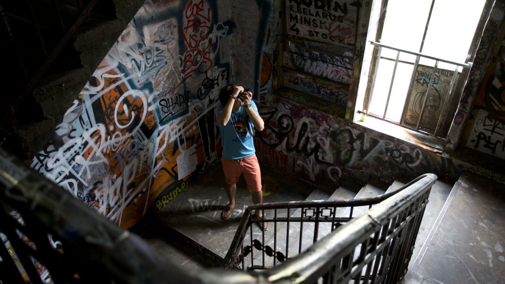 Travel photography tips for beginners - man photographing graffiti on a dark staircase