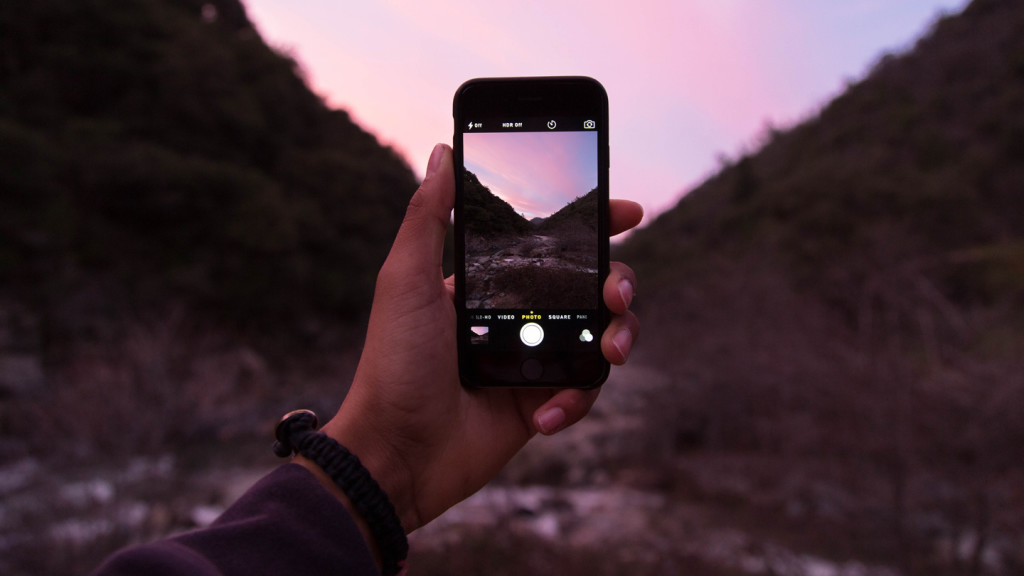 Cut the corners with our travel photography tips for beginners and you'll be upping your photography game in no time - hand holding up iphone to capture sunset