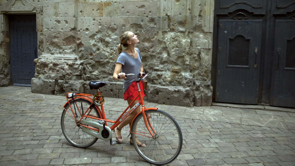 self improvement - image of a girl pushing a bike through a street in Barcelona