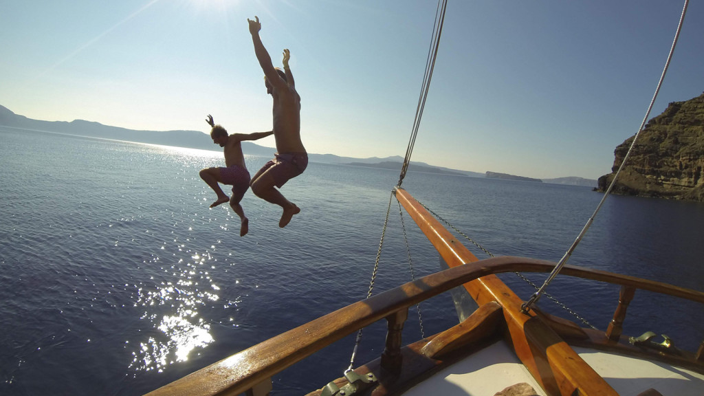 adventure travel - image of two boys jumping from a boat