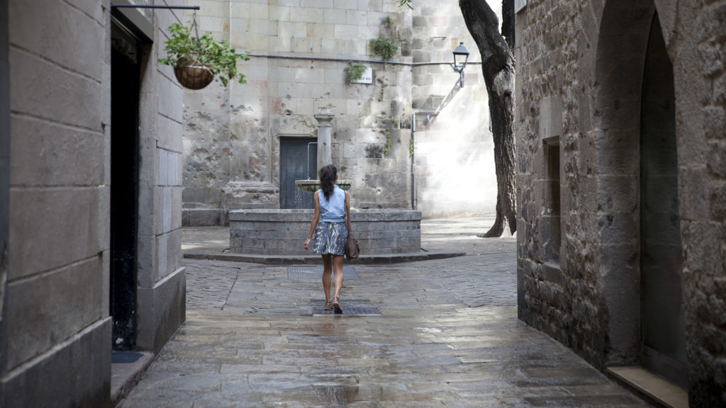adventure travel - image of a girl walking through an empty street in Barcelona