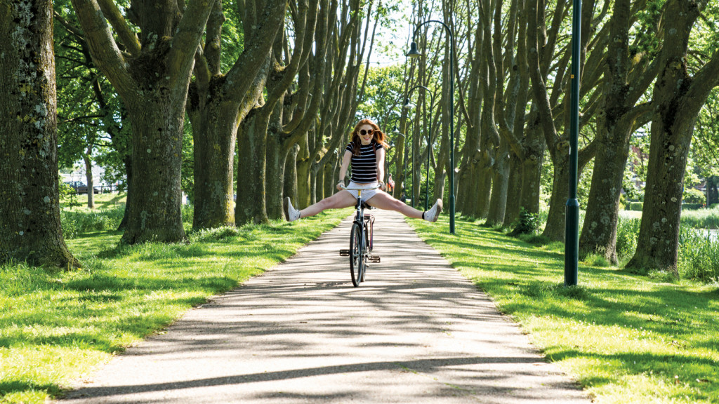 things to do before you die - image of a girl riding a bike in amsterdam