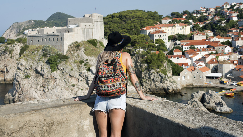 trip to europe - girl looking over city walls in dubrovnik