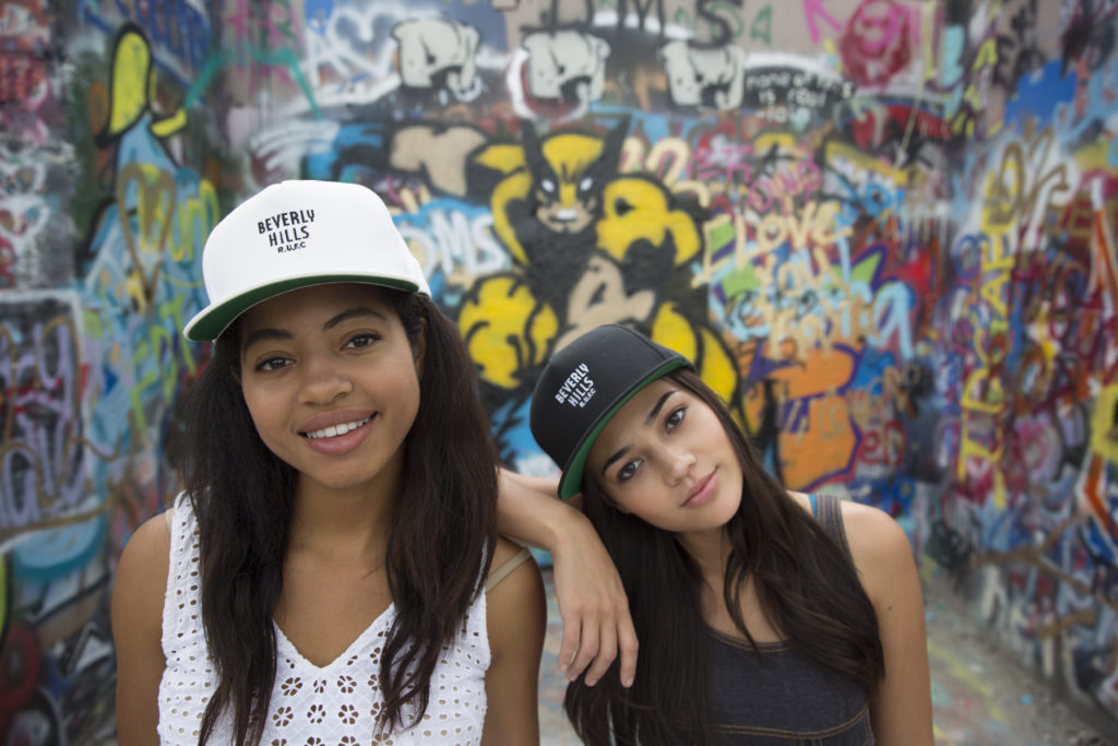 girls in baseball caps smiling to camera