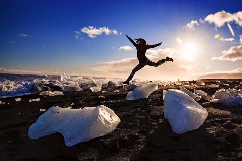 girl leaping over ice in Iceland