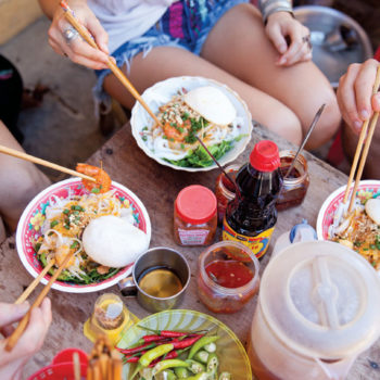Chopsticks over table of Asian food