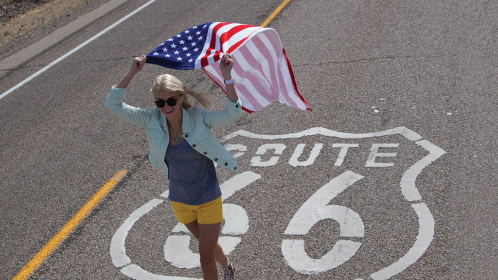 girl walking on route 66 road sign waving flag
