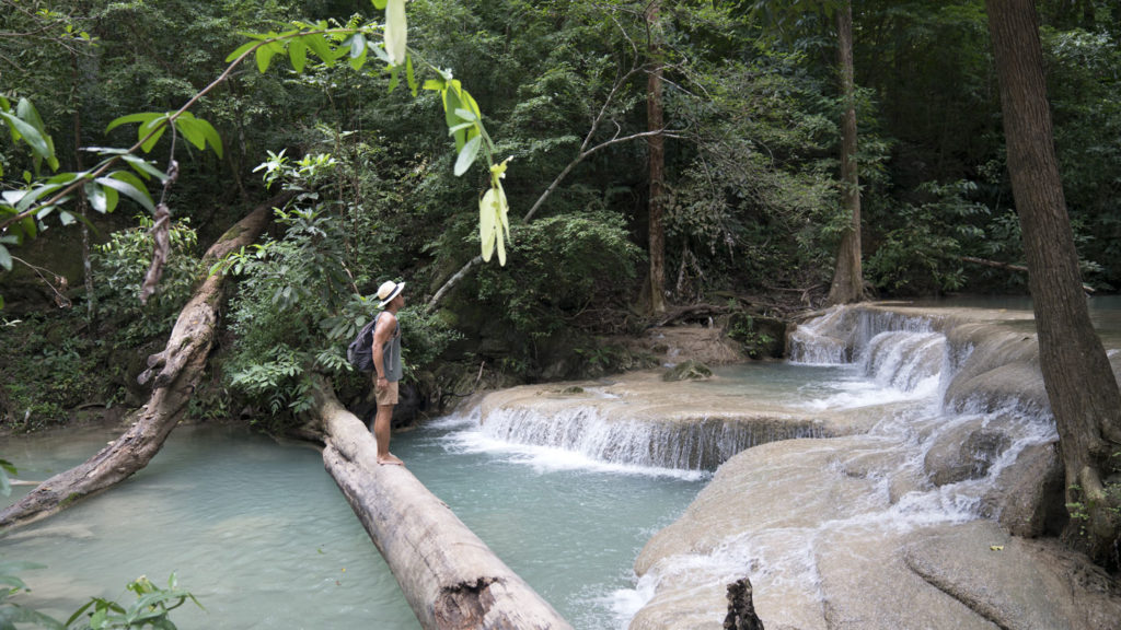 man standing on log by waterfall