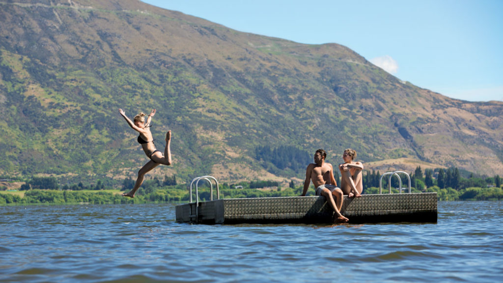 group jumping off jetty in New Zealand