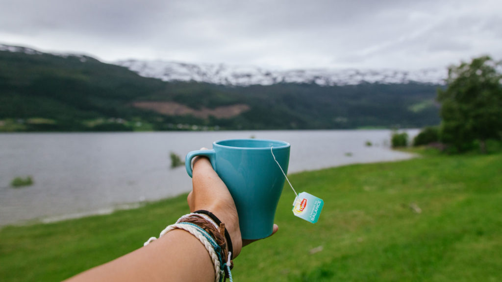 hand holding a cup of tea in front of camera in Norway