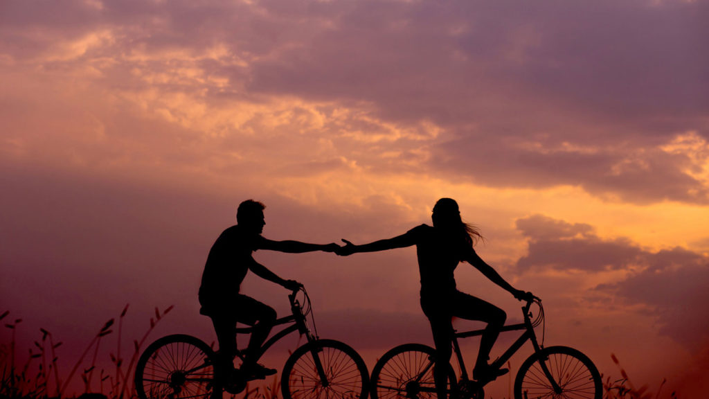 two friends cycling at sunset