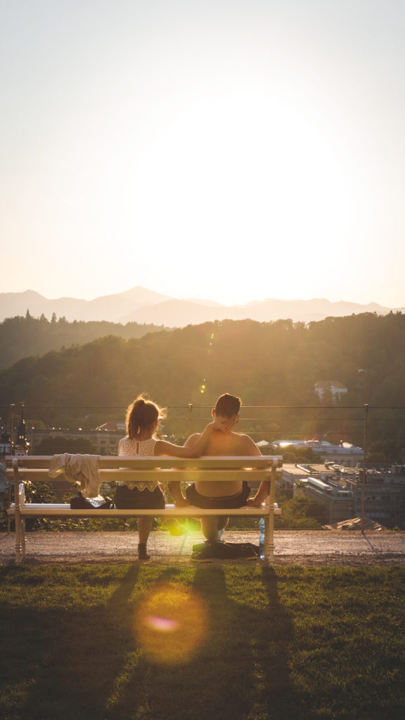 couple sitting on bench watching the sun set, photographed by earth Focus