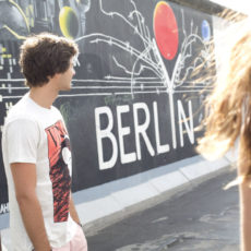 Two people in front of graffiti