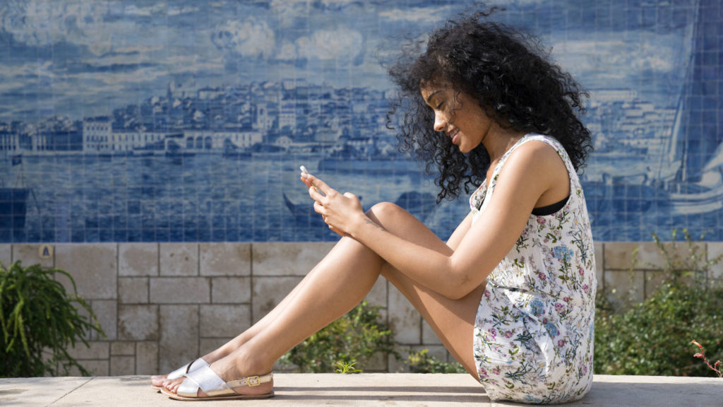 girl texting on Lisbon - digital nomad lifestyle