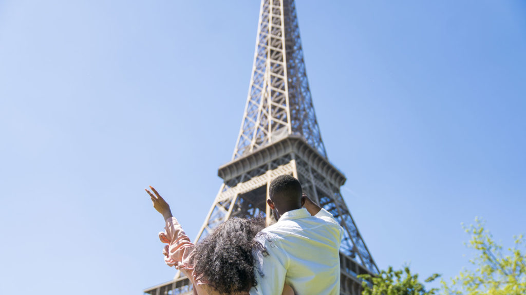 couple standing by the eiffel tower