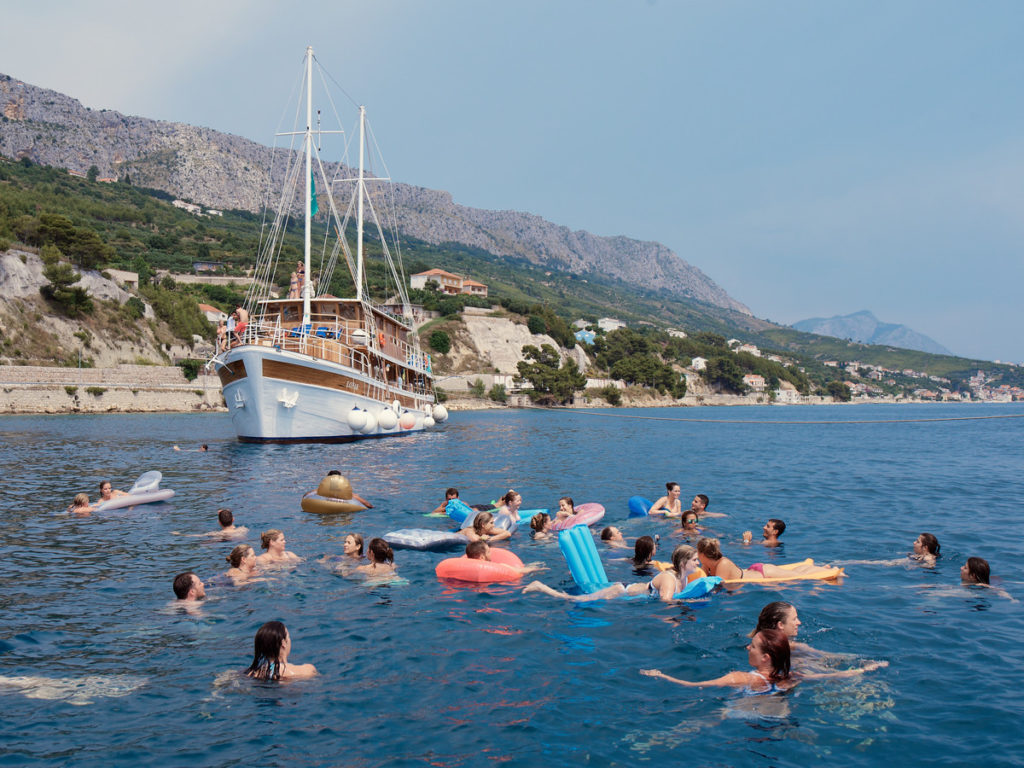Group swimming near a boat - things to do in croatia