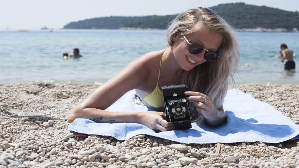 Girl-on-beach-with-film-camera-disposable-camera-sales