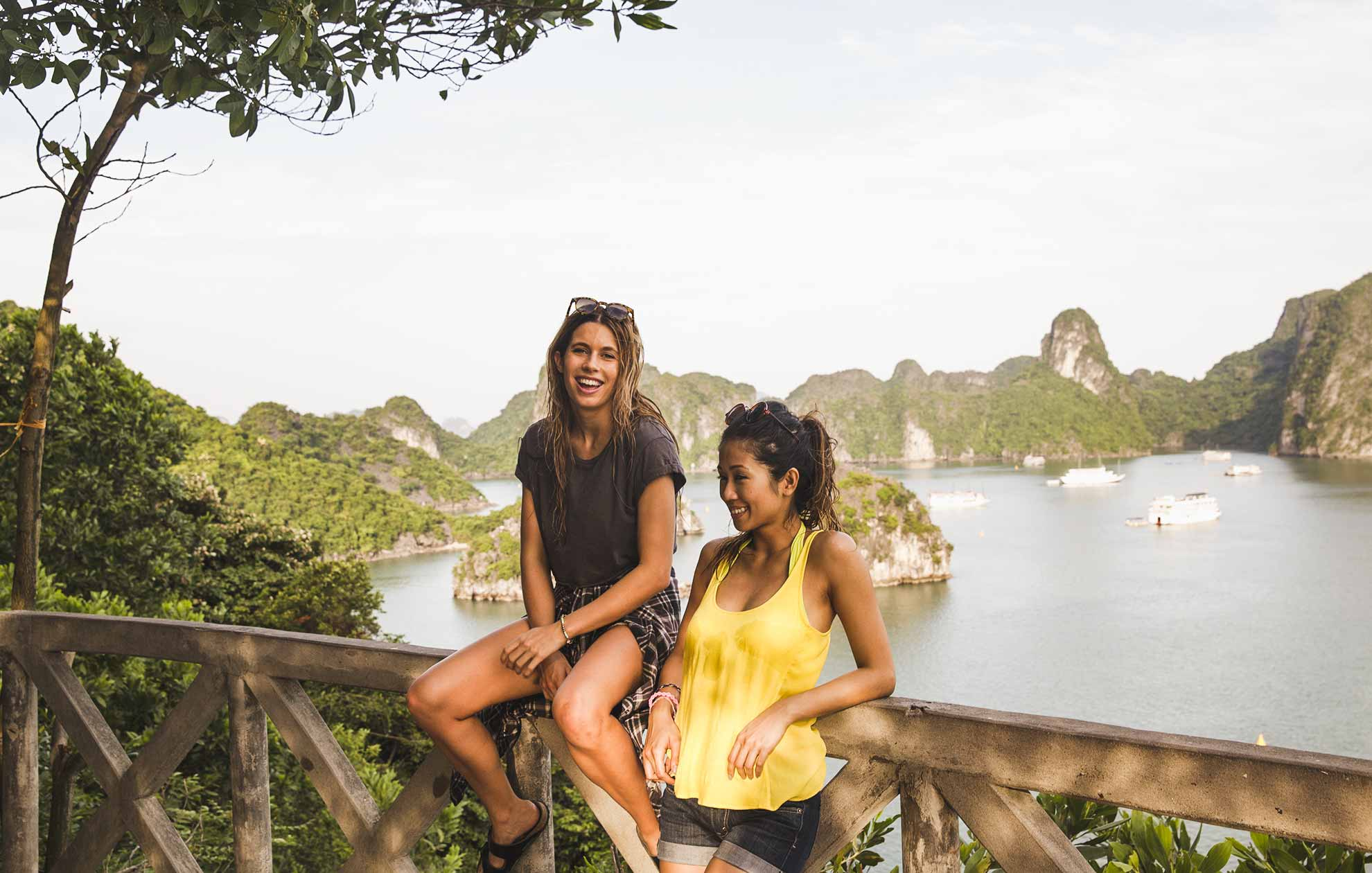 two young women standing by balcony overlooking Ha Long Bay