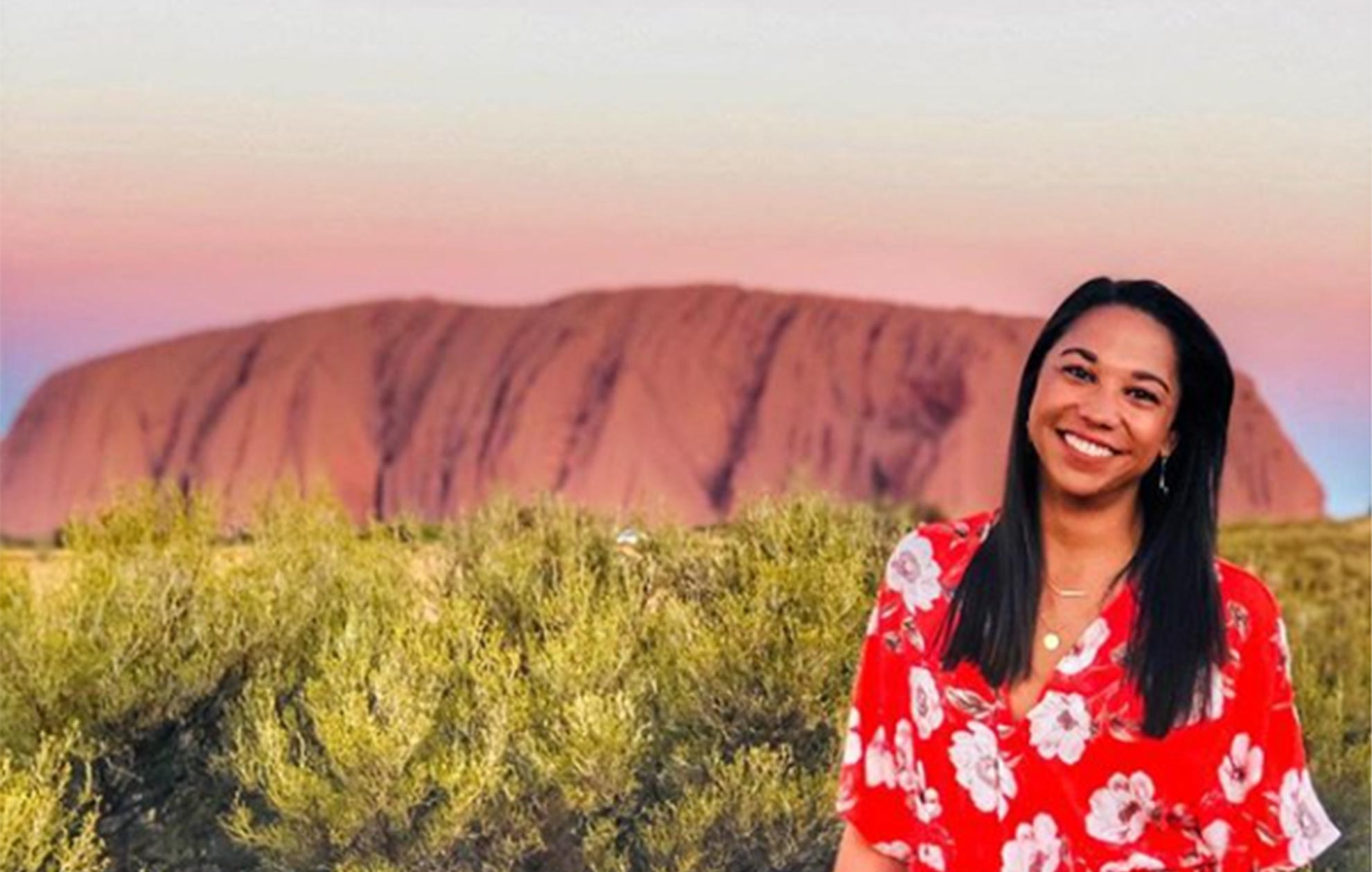 young woman standing in front of Uluru