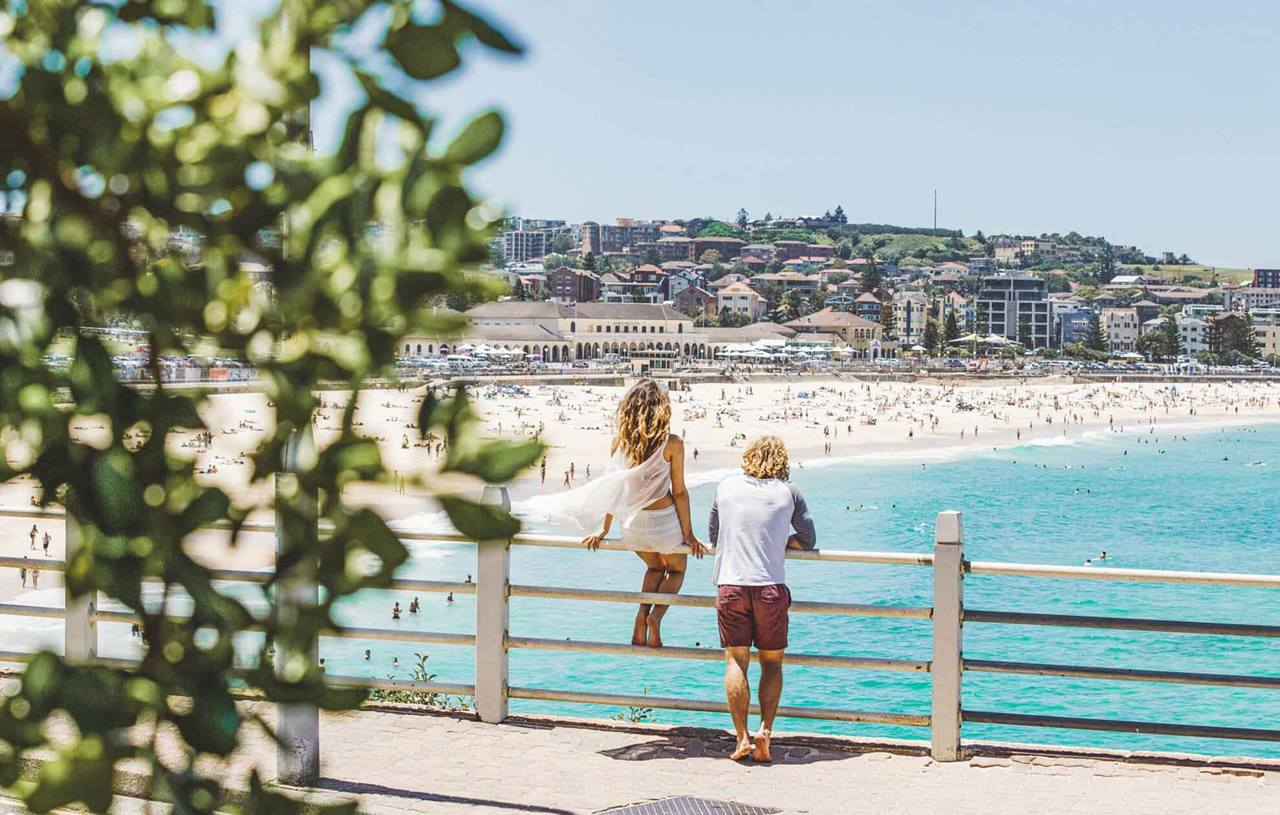 young man and women looking at view of Bondi Beach