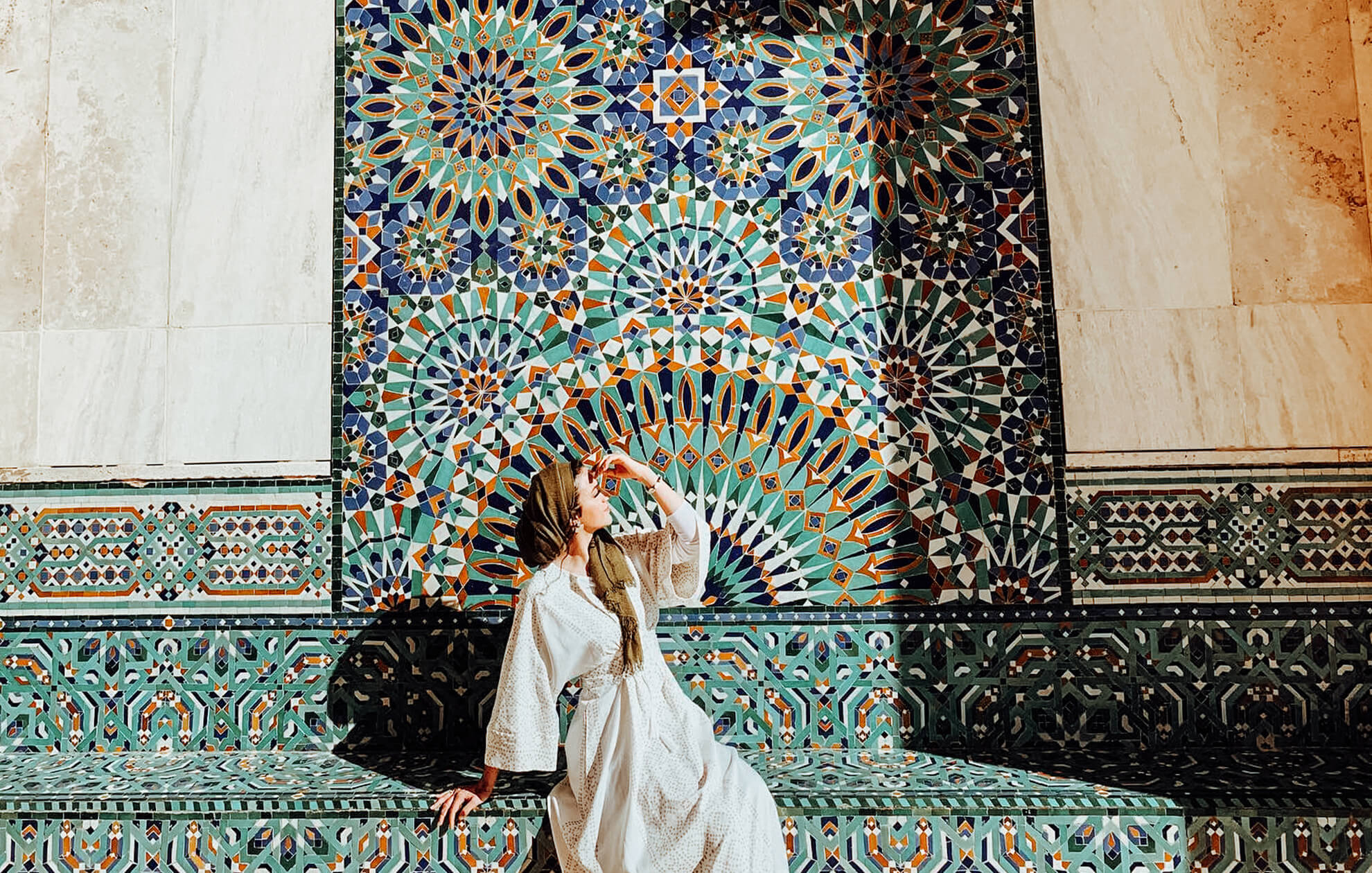 young women posing in front of mosaic tiled wall