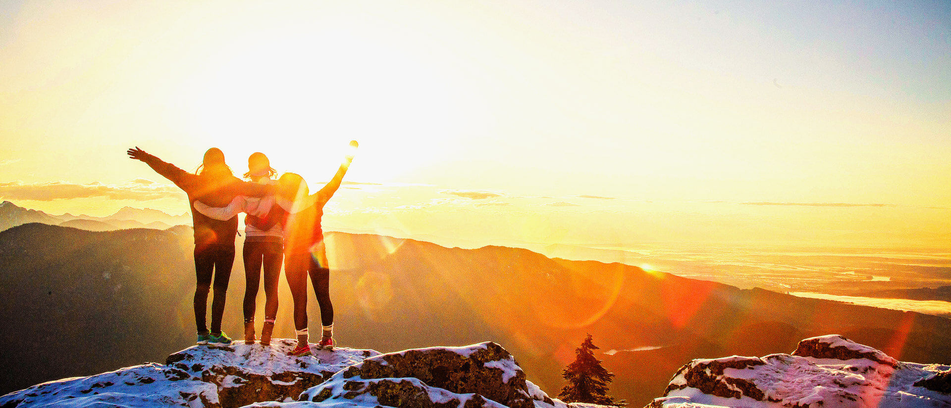 three young people standing at the top of a snow capped mountain at sunrise