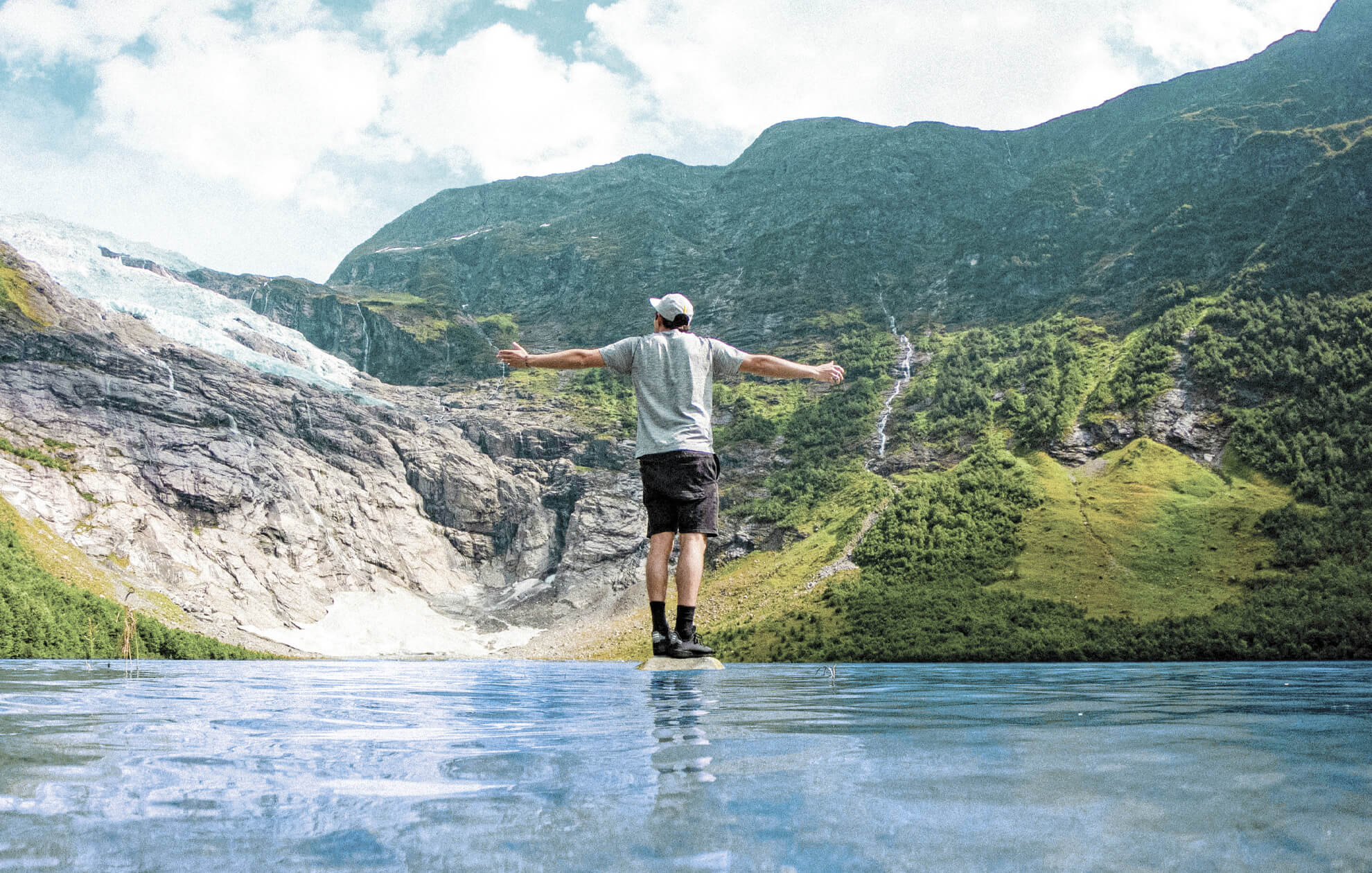 man standing arms outstretched on a rock in a river in front of a waterfall