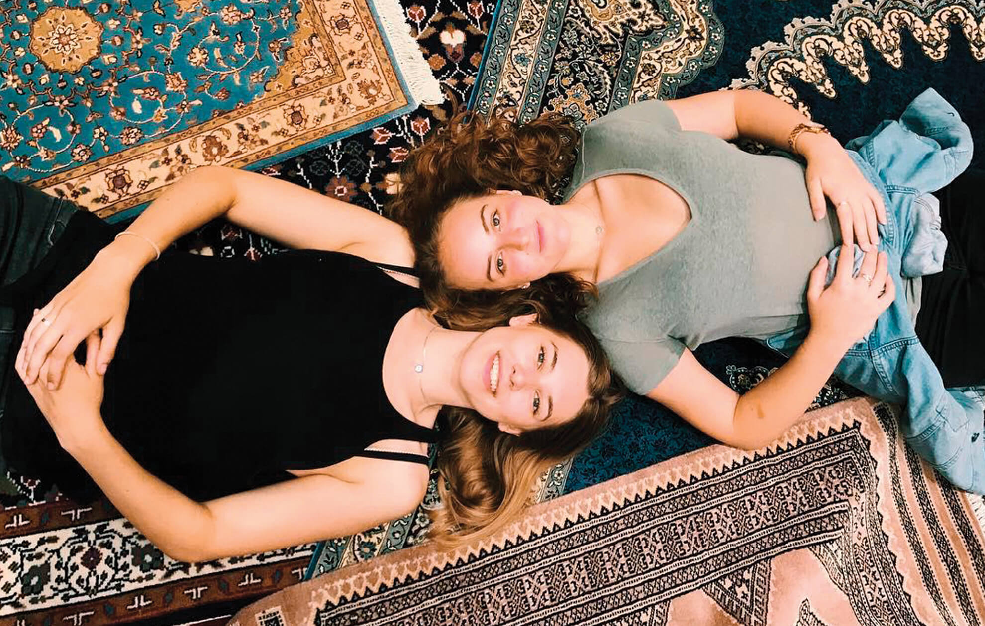 Two girls laying on traditional carpets in Morocco