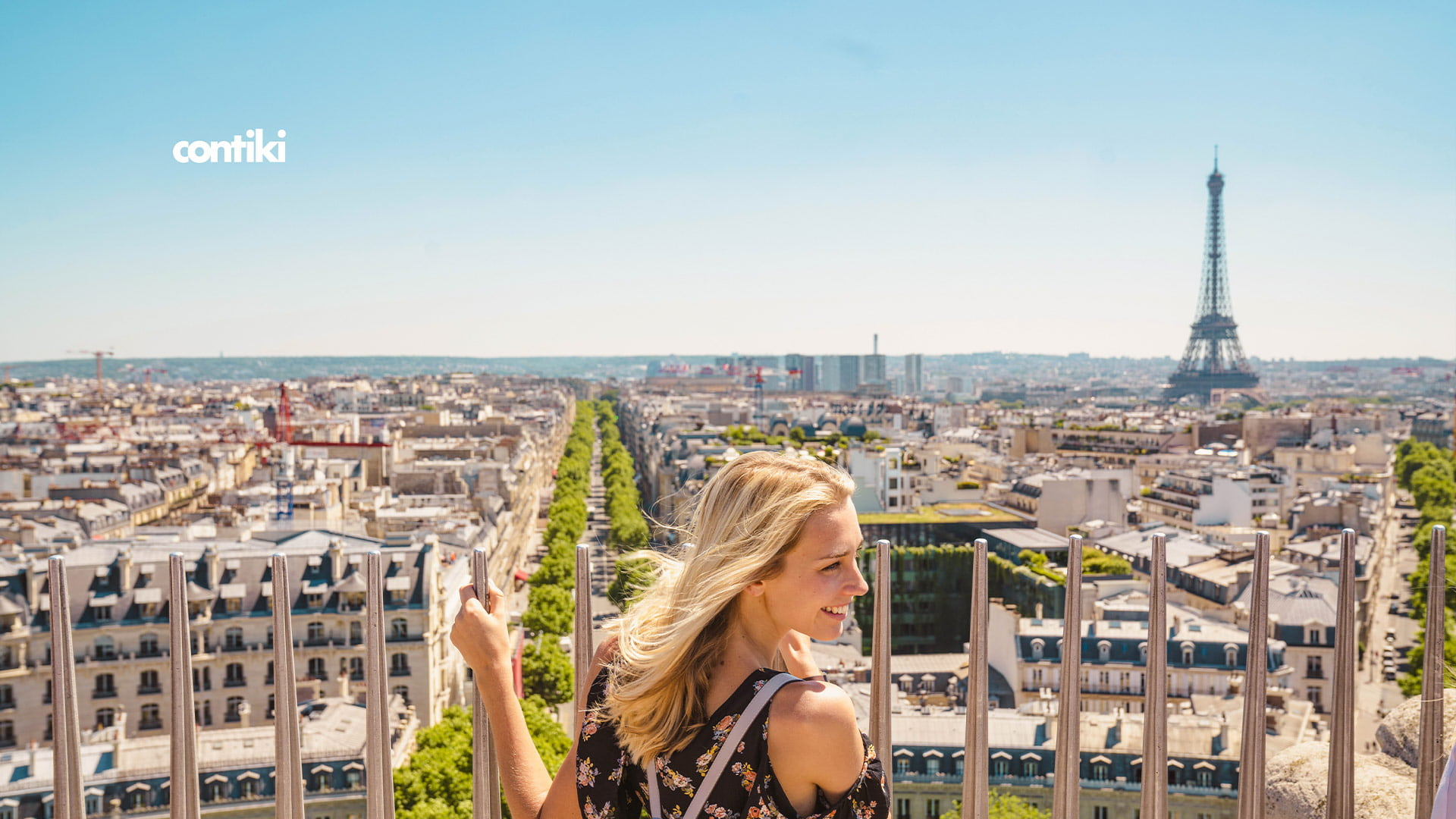 close-up image of a blonde young female traveler admiring Paris from up top